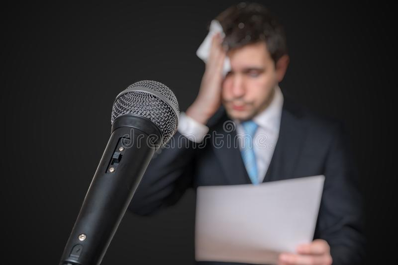 Microphone in front of a nervous man who is afraid of public speech and sweating.  royalty free stock image