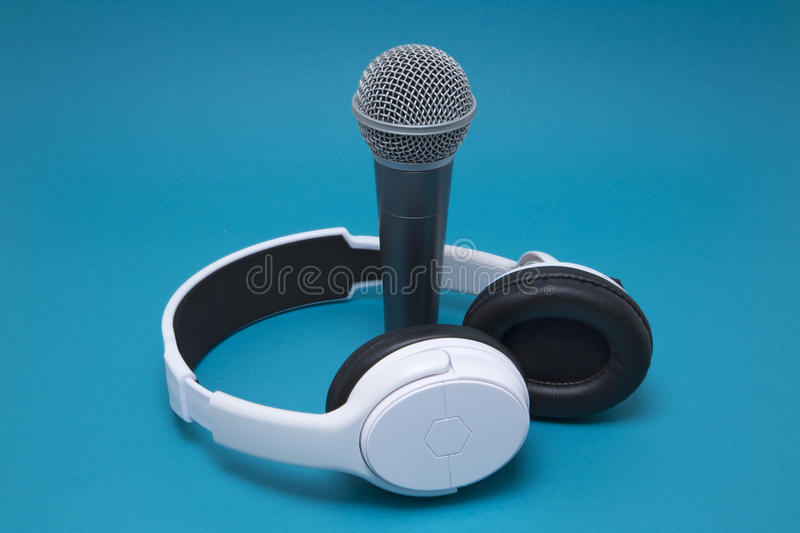 Microphone and headphones. Professional microphone and headphones on a blue background royalty free stock photography