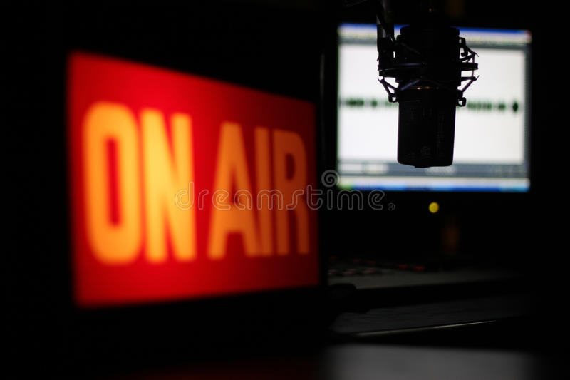 Microphone Interview. Radio studio with focus on the microphone and the interview about to unfold. Images features illuminated On Air sign and wave form monitor
