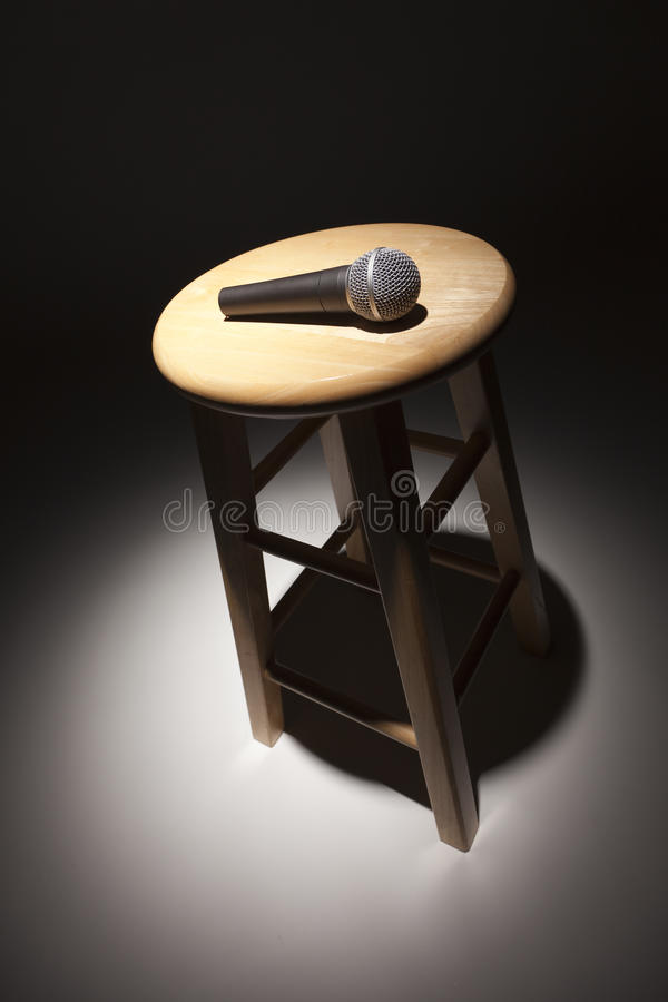 Microphone Laying on Wooden Stool Under Spotlight. Abstract royalty free stock images