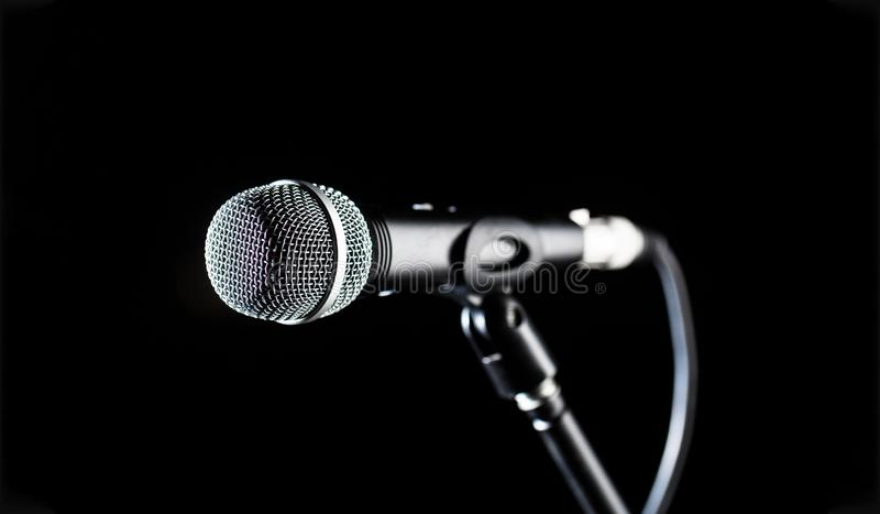 Microphone, mic, karaoke, concert, voice music. Closeup microphone. Vocal audio mic on a bleck background. Live music royalty free stock photo