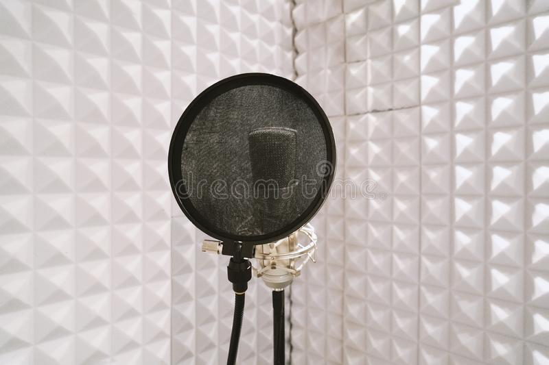 Microphone on mic stand in soundproof isolation booth for vocal recording at sound studio. Microphone with pop filter on mic stand in soundproof isolation booth stock image