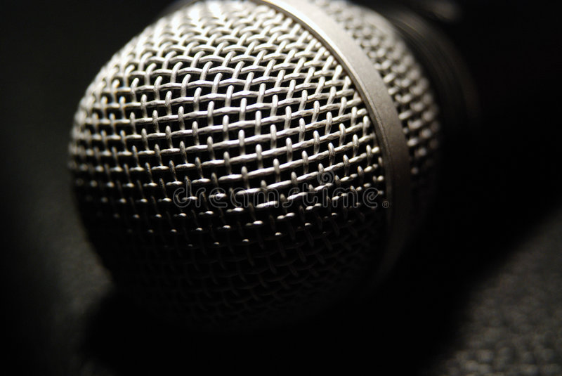 Microphone closeup. Showing protective wire grid (with openings for sound), dark background royalty free stock image