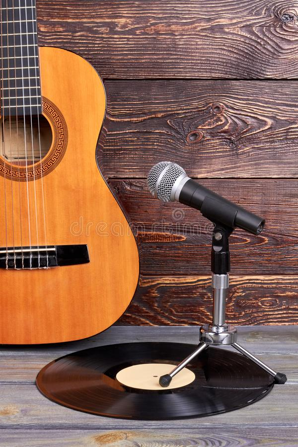 Microphone on old vinyl record. Acoustic guitar, vintage vinyl disk and microphone on textured wooden surface stock photo