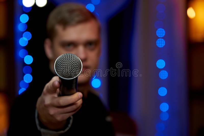 A microphone in the outstretched hand of a blurry young man. Copy space royalty free stock image