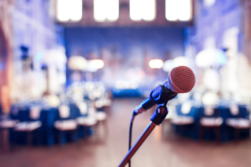 Microphone over the Abstract blurred photo of conference hall or wedding banquet background royalty free stock image