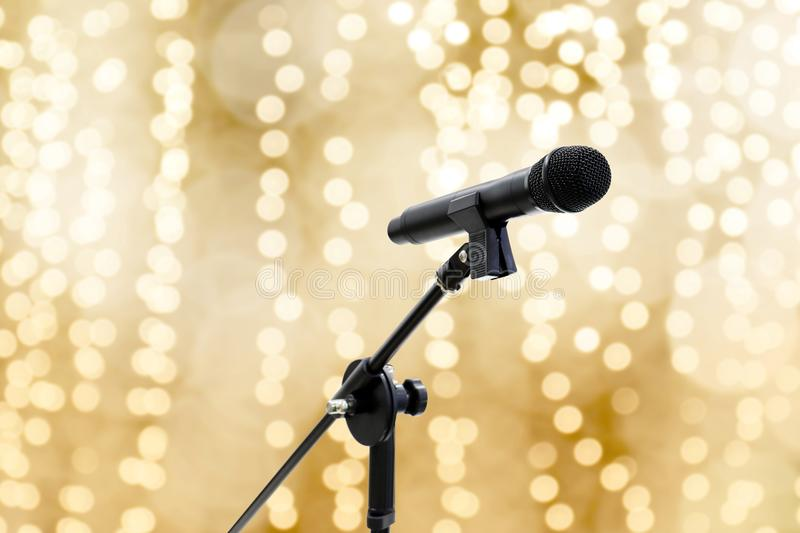 Microphone over blur gold yellow bokeh golden background beautiful romantic or luxury glitter lights circle soft pastel shade. The Microphone over blur gold royalty free stock photos
