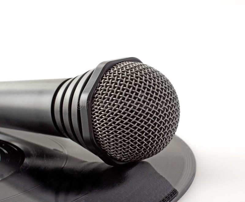 Microphone over vinyl. A lonely black microphone over a vinyl record royalty free stock image