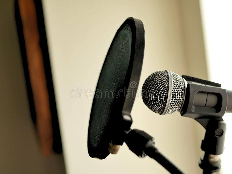 A microphone and pop filter set up in recording studio vocal booth. stock photo