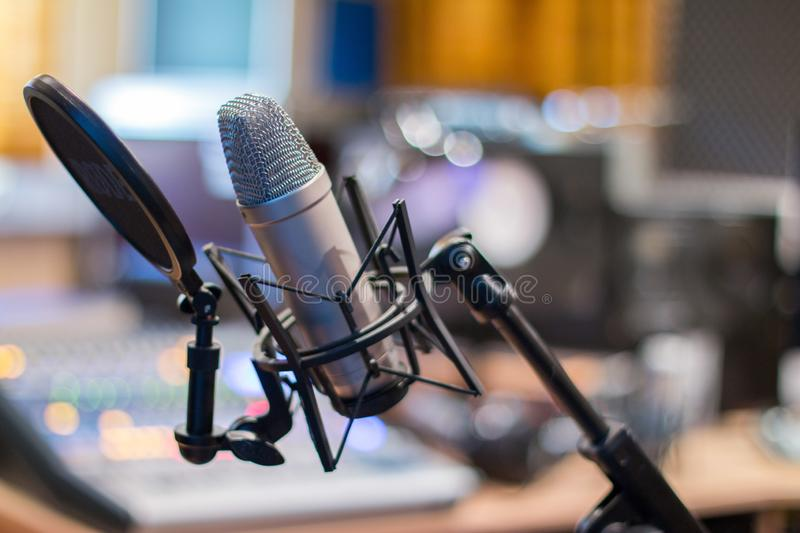 Microphone in a professional recording or radio studio, equipment in the blurry background. Professional studio microphone, recording studio, equipment in the royalty free stock photo