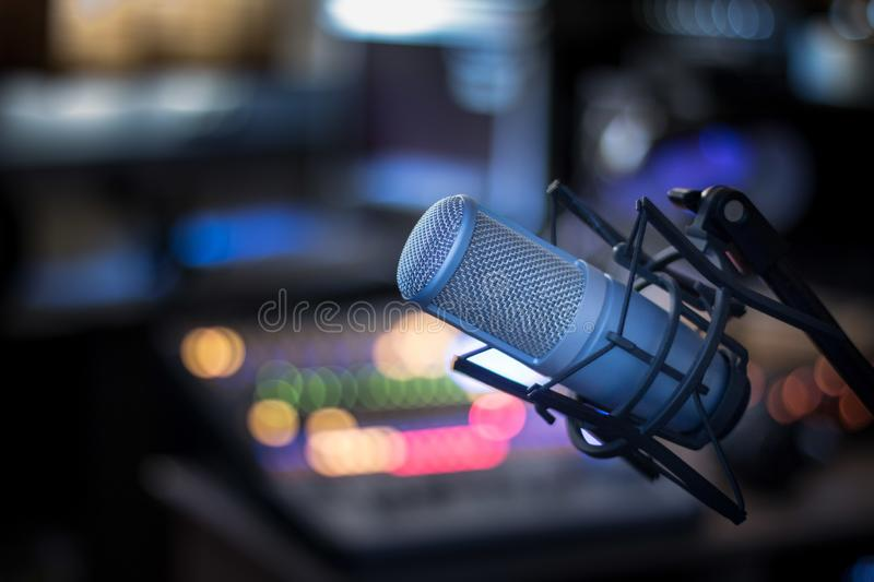Microphone in a professional recording or radio studio, equipment in the blurry background. Professional studio microphone, recording studio, equipment in the royalty free stock images