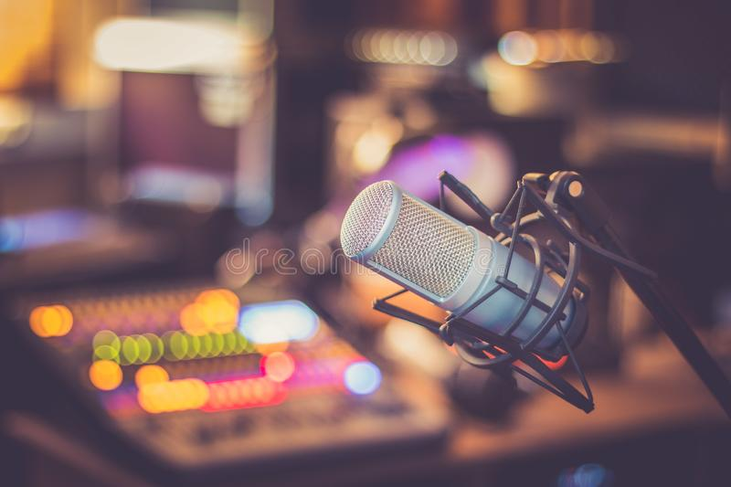 Microphone in a professional recording or radio studio, equipment in the blurry background. Professional studio microphone, recording studio, equipment in the stock image