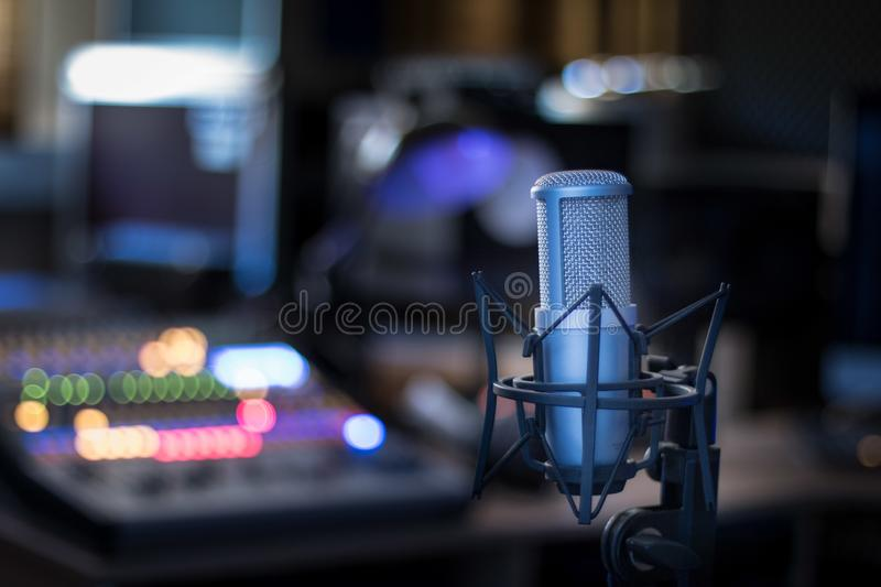 Microphone in a professional recording or radio studio, equipment in the blurry background. Professional studio microphone, recording studio, equipment in the stock photos