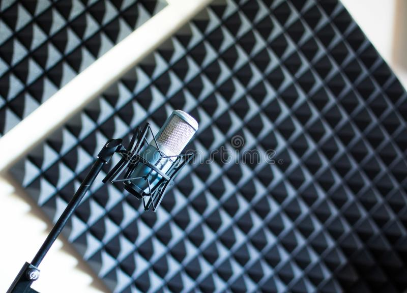 Microphone in a professional recording or radio studio, sound insulation in the blurry background. Professional studio microphone in a recording studio, sound royalty free stock photography