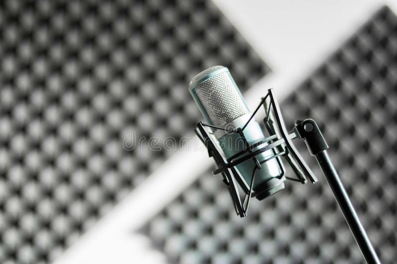 Microphone in a professional recording or radio studio, sound insulation in the blurry background. Professional studio microphone in a recording studio, sound stock photography
