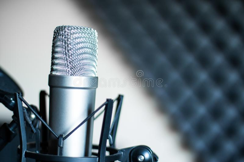 Microphone in a professional recording or radio studio, sound insulation in the blurry background. Professional studio microphone in a recording studio, sound stock photos