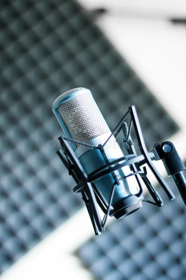 Microphone in a professional recording or radio studio, sound insulation in the blurry background. Professional studio microphone in a recording studio, sound royalty free stock photos