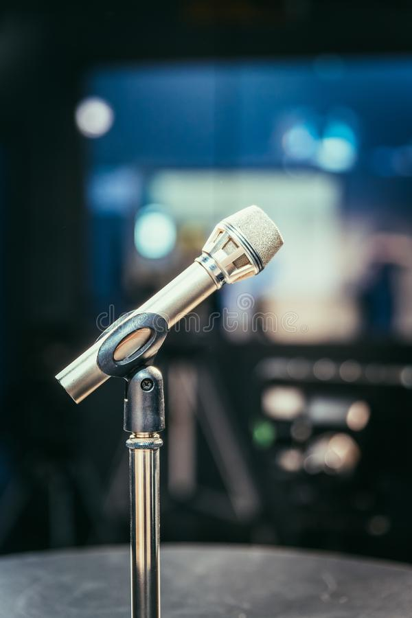 Microphone in the recording studio, equipment and lighting in the blurry background royalty free stock image