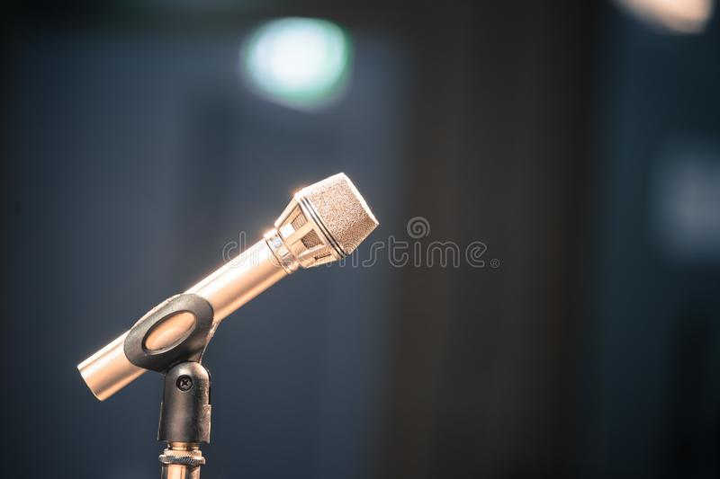 Microphone in the recording studio, equipment and lighting in the blurry background. Metal microphone in the studio, studio lights in the blurry background stage royalty free stock photos
