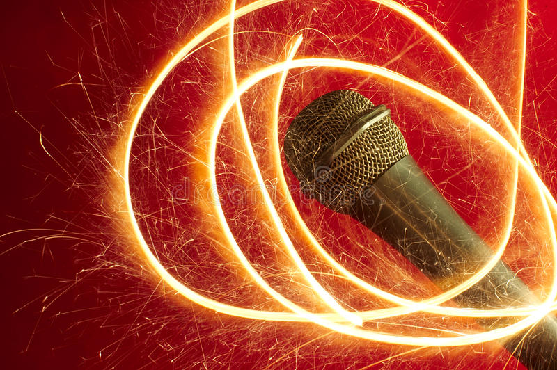 Microphone on red background and sparkler stock images