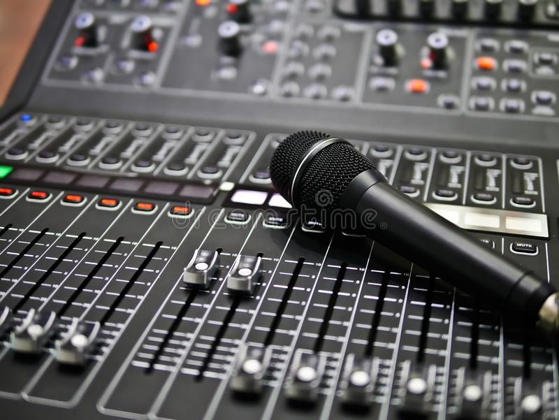 Microphone rests on an audio mixer controller in the control room, Sound mixer control for live music and studio equipment, music stock photo