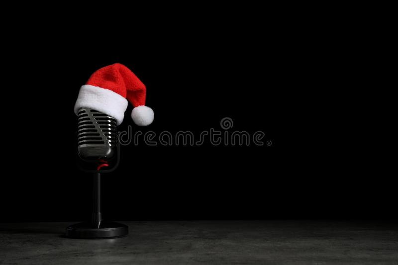 Microphone with Santa hat on grey stone table against black background. Christmas music. Microphone with Santa hat on grey stone table against black background royalty free stock image