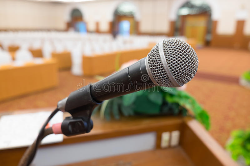 Microphone in seminar. Microphone over the Abstract blurred photo of seminar room background royalty free stock photography