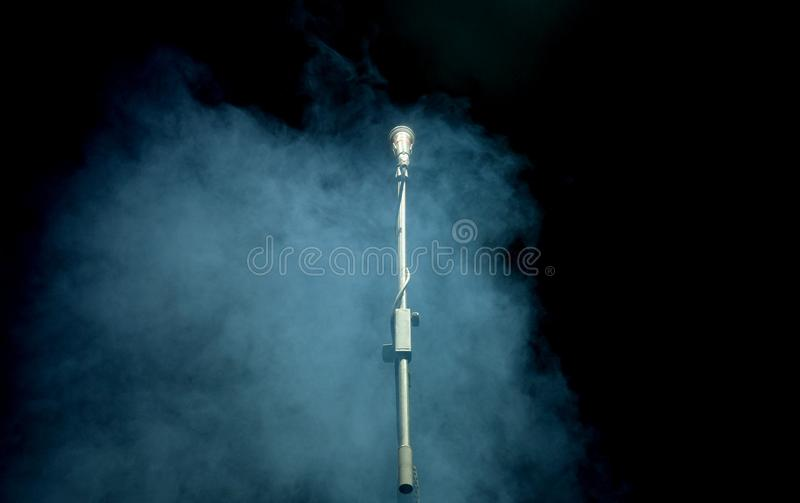 Microphone in a smoke on a dark background. In club royalty free stock image