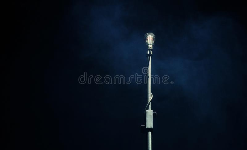 Microphone in a smoke on a dark background. In club stock photo