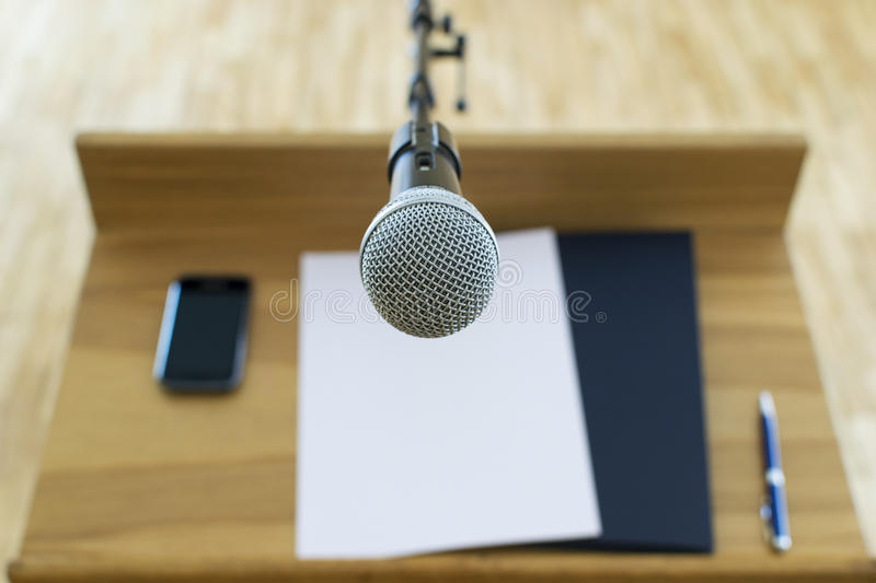 Microphone at the speech podium. First person view of the microphone at the speech podium royalty free stock photos