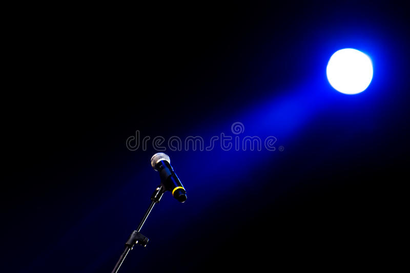 Microphone and Stage Light. Blue stage light lightining a icrophone stock images
