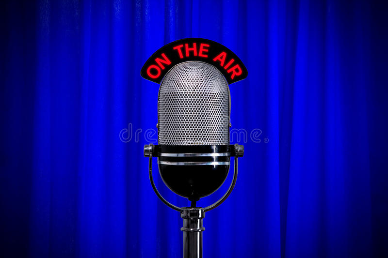 Microphone on stage with spotlight on blue curtain royalty free stock photography