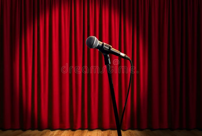Microphone on stage under spotlights with red curtain royalty free stock photos