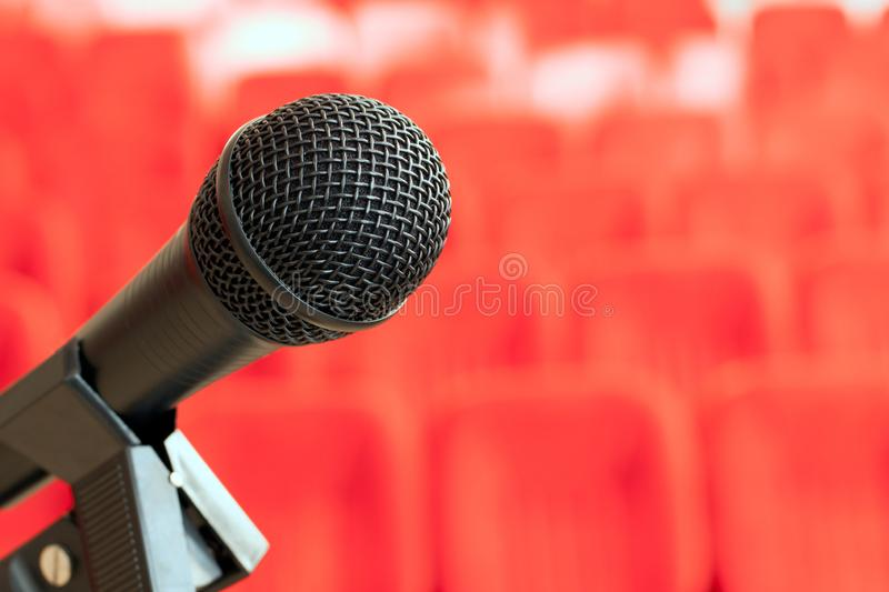 Microphone on the stand in an empty assembly hall with red chairs. concept of trainings, business meetings and conferences. Bright red background royalty free stock photography