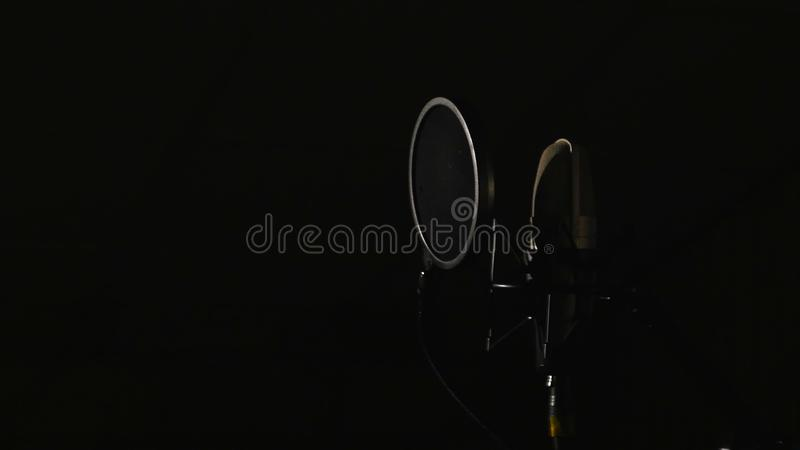 Microphone on a stand located in a music studio recording booth under low key light.  stock photography