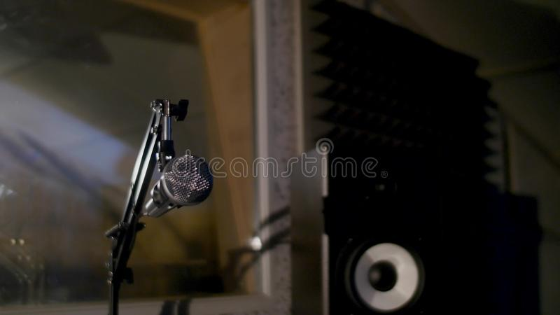Microphone on a stand located in a music studio recording booth under low key light.  royalty free stock photography