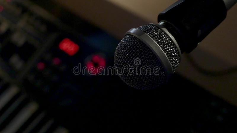 Microphone on a stand located in a music studio recording booth under low key light.  royalty free stock images