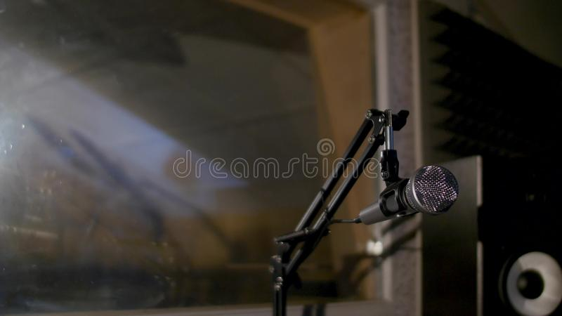 Microphone on a stand located in a music studio recording booth under low key light.  royalty free stock photo