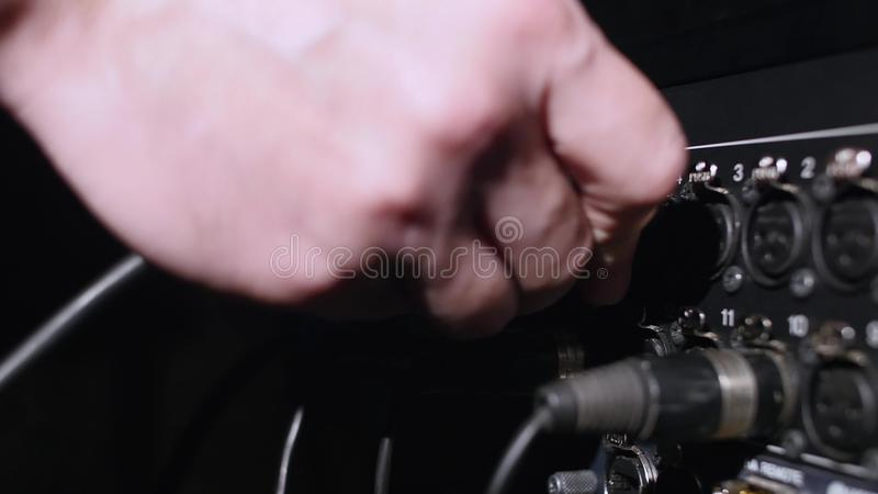 Microphone on a stand located in a music studio recording booth under low key light.  stock images