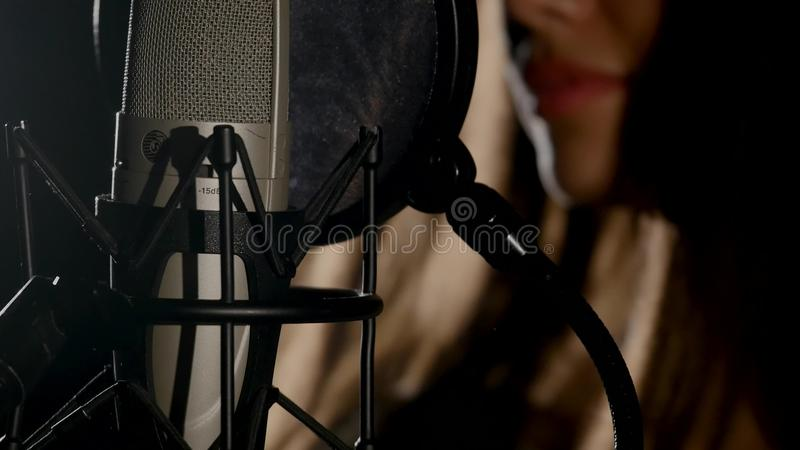 Microphone on a stand located in a music studio recording booth under low key light.  stock image