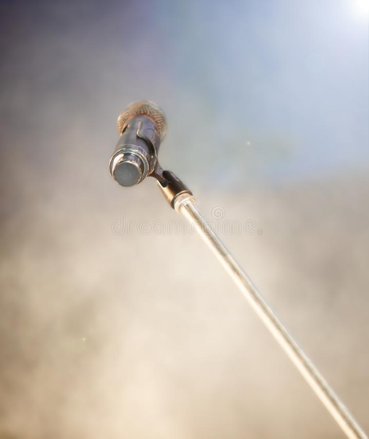 Microphone with stand on stage lamp and lighting. Over blur background of density of puffy smoke foggy, copyspace royalty free stock image