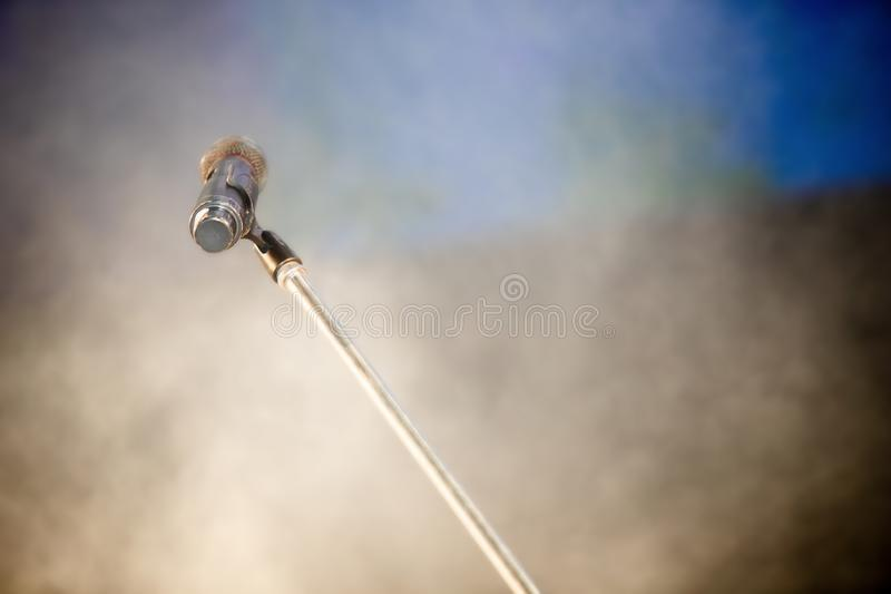Microphone with stand on stage lamp and lighting. Over blur background of density of puffy smoke foggy, copyspace stock images