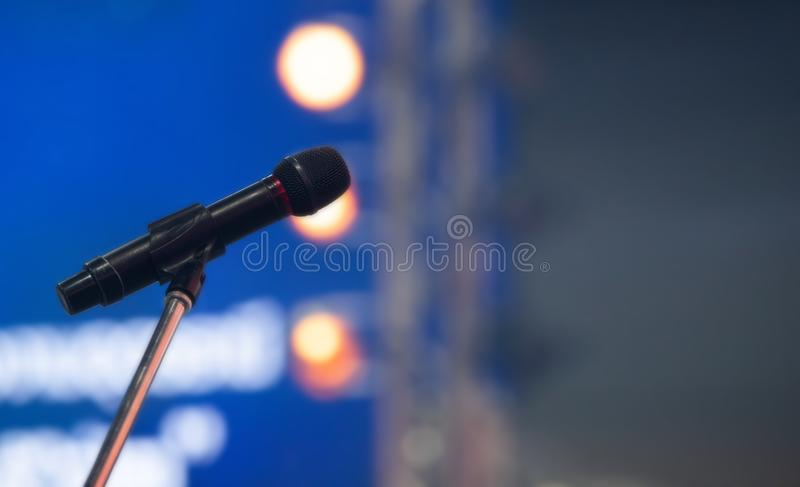 Microphone with stand on stage lamp and lighting. Over blur background of density of puffy smoke foggy, copyspace royalty free stock photo