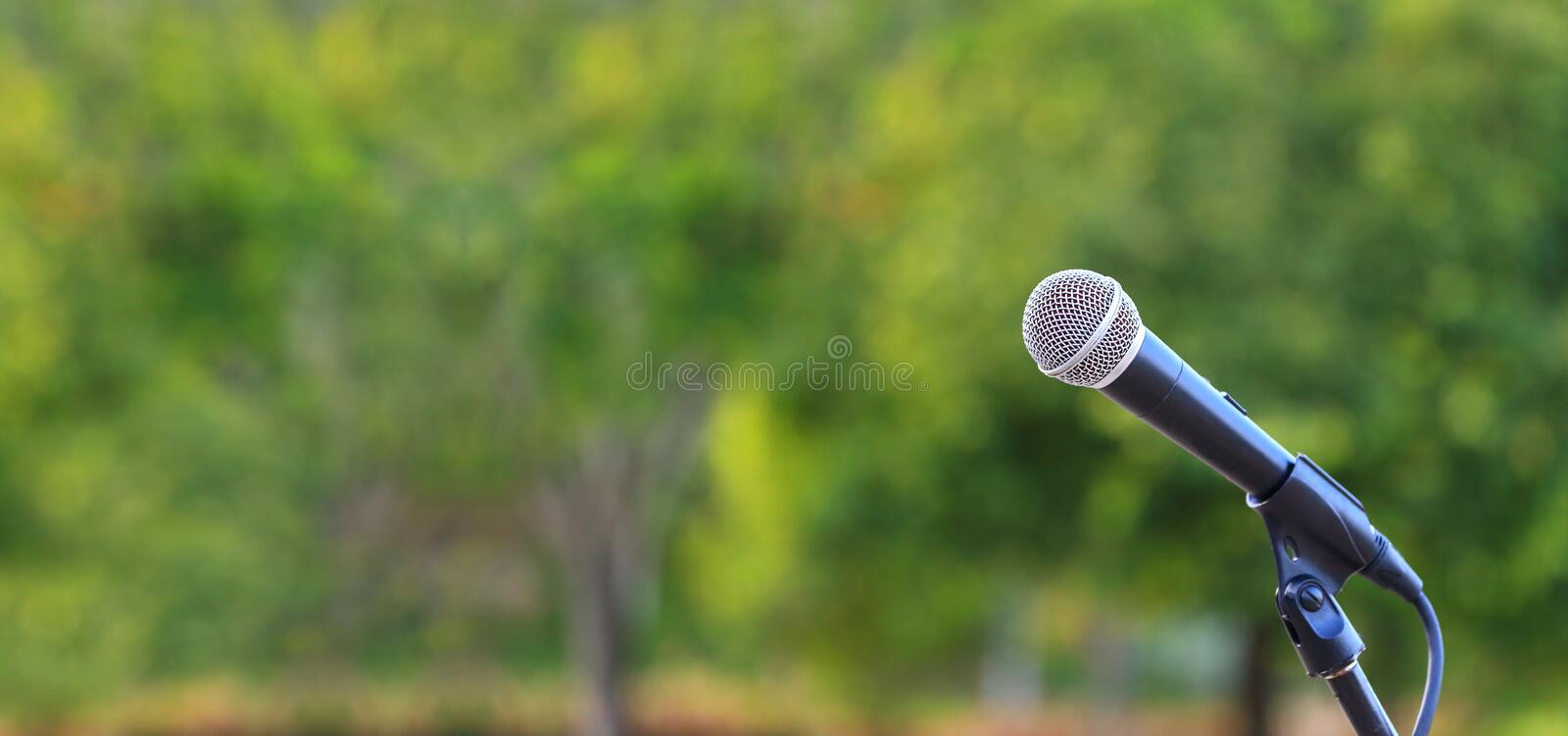 Microphone standing for speaker on the outdoor natural setting for music, concert and environmental awareness talk with copy space royalty free stock photography