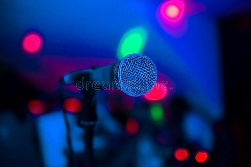 Microphone stands on stage in a nightclub. Bright club light shines on MIC. Performances in the night club stock images