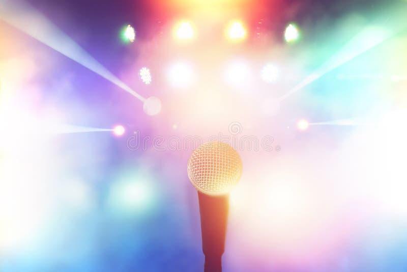 Microphone sur l'étape dans la salle de concert avec la lumière colorée brouillée photographie stock libre de droits
