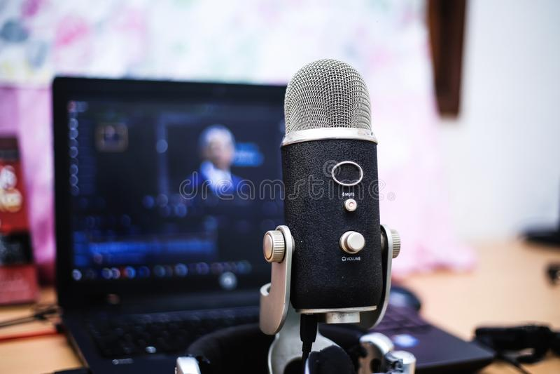 Microphone sur la table avec l'ordinateur portable au fond photo stock