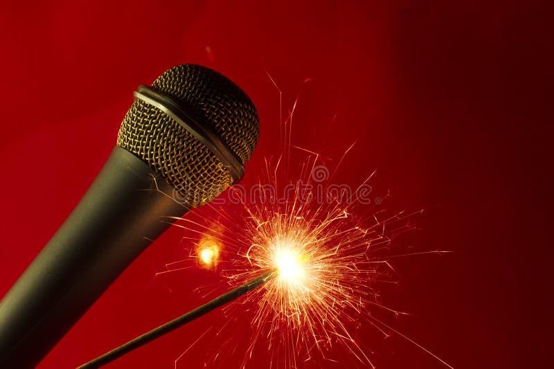 Microphone sur le fond et le sparkler rouges photographie stock