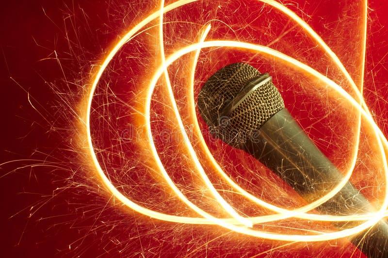 Microphone sur le fond et le sparkler rouges images stock