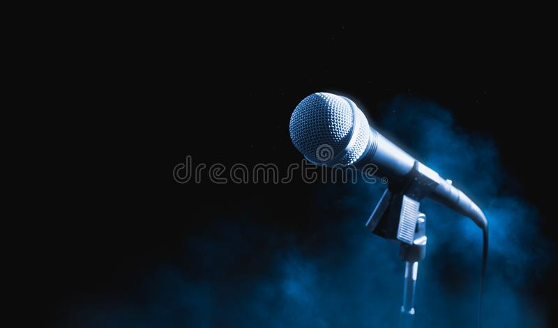 Microphone sur un support sur un fond foncé avec de la fumée images stock